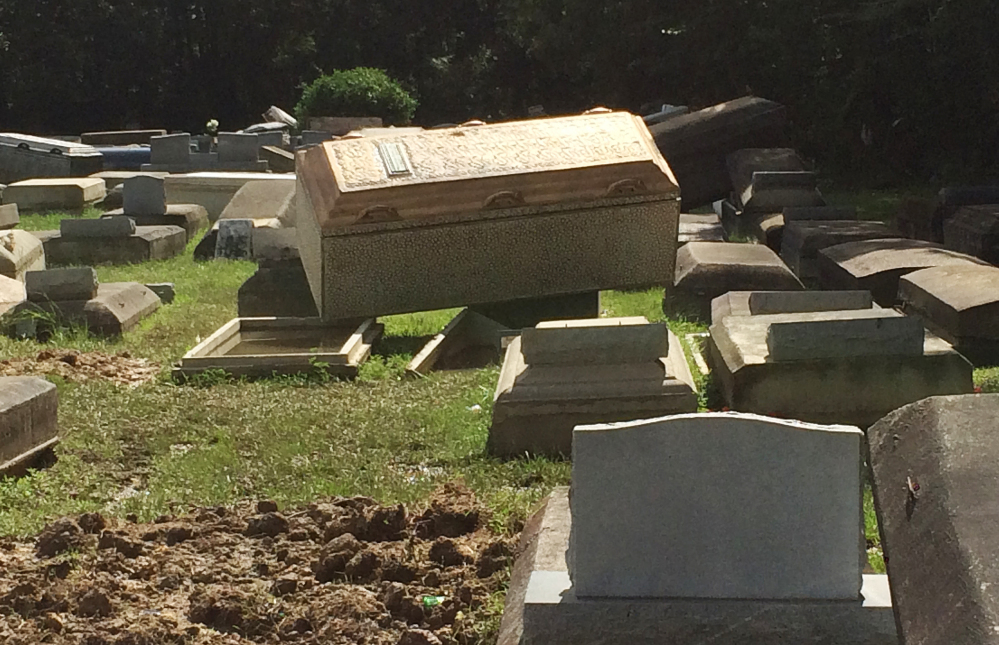 Coffins lie unearthed Thursday in Plainview Cemetery in Denham Springs, La.