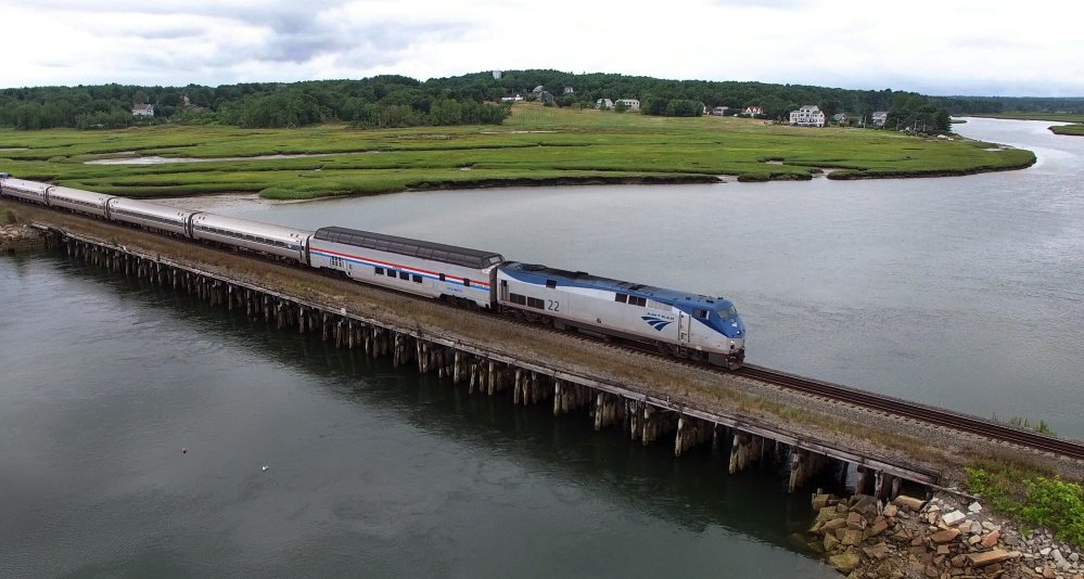Amtrak's dome car, with the red, white and blue markings, is first in the line of passenger cars as the Downeaster travels through the Scarborough Marsh. The dome car hasn't been used on the Downeaster line before.