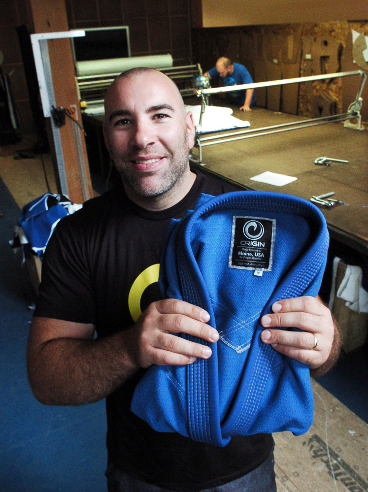 OriginUSA owner Peter Roberts holds a martial arts gi made at his manufacturing facility in Industry. Employee Jon Milan cuts fabric in background.