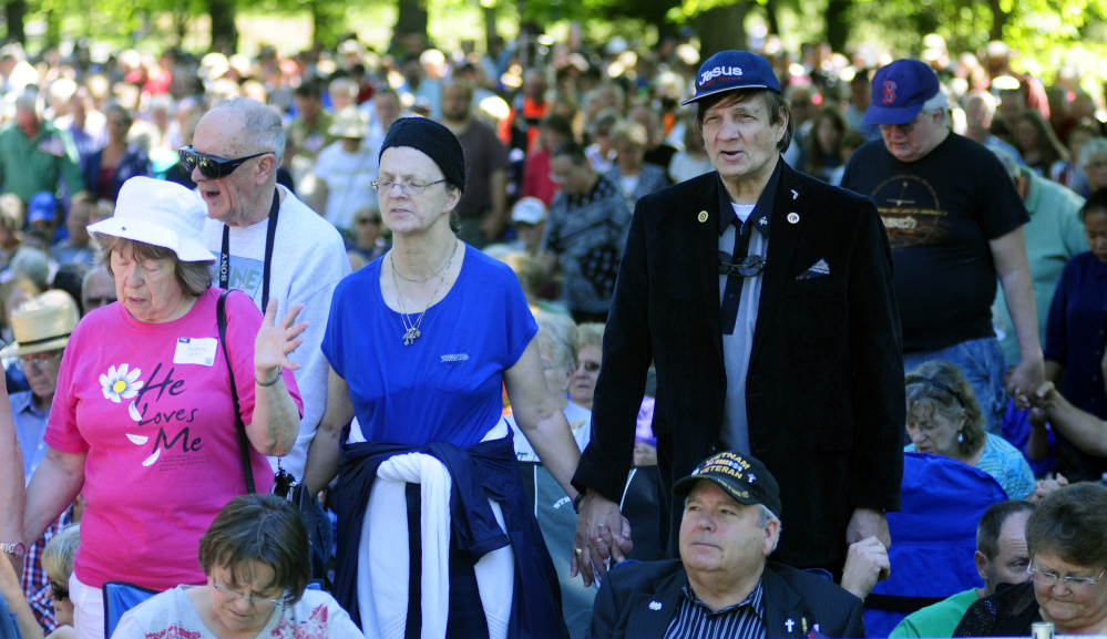 People pray during a rally led by Franklin Graham, the president of Samaritan's Purse and the Billy Graham Evangelistic Association, in Capitol Park on Tuesday in Augusta on his Decision America Tour. The park is across the street from the Maine State House.