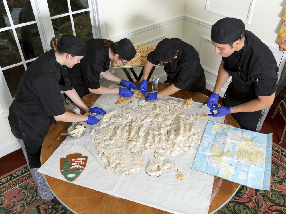 Emily Kennedy, left, Stacy Lapingcao, Zack Brinker and Eduardo Lopez consult a map of Mount Desert Island to sculpt topographical features made with a Rice Krispies mix covered in fondant.