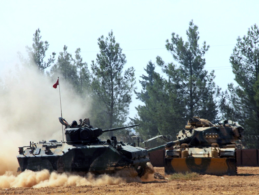 A Turkish army tank and an armored vehicle maneuver near the Syrian border in Karkamis, Turkey, on Tuesday. Hundreds of fighters backed by Turkey are preparing for an assault on a town in northern Syria held by the Islamic State group.