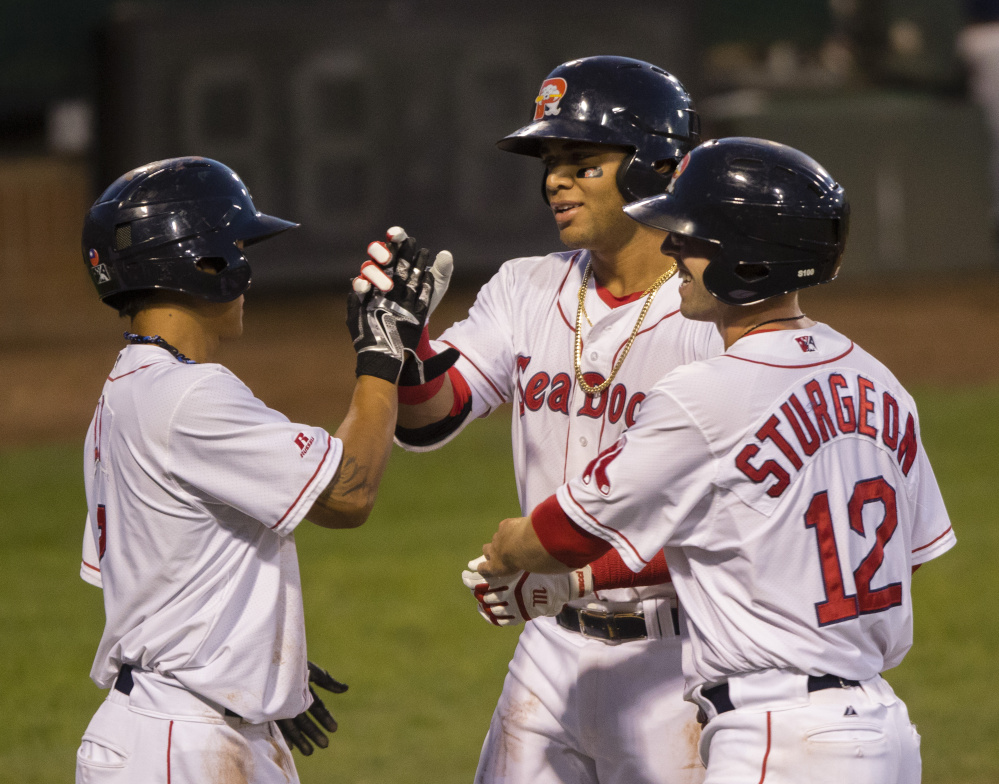 PORTLAND, ME - AUGUST 23: Portland Sea Dogs batter Yoan Moncada is congratulated by teammates Tzu-Wei Lin (L) and Cole Sturgeon after he knocked them in with a 2nd inning home run against the New Hampshire Fisher Cats in AA baseball action at Hadlock Field in Portland on August 23, 2016 . (Photo by Carl D. Walsh/Staff Photographer)