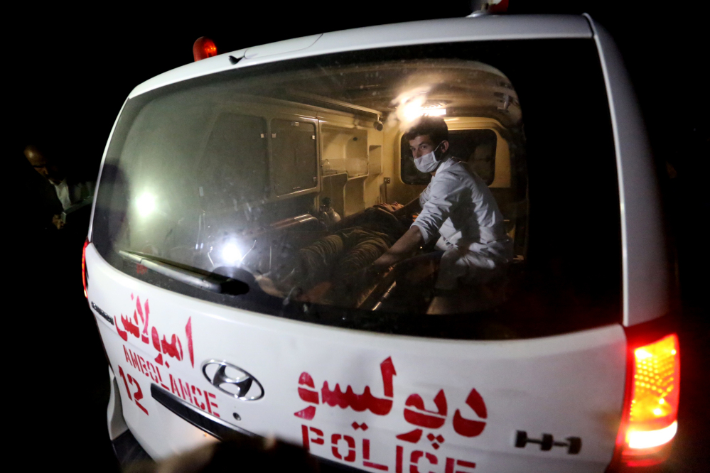 A wounded man is assisted in an ambulance after an attack by militants on the campus of the American University of Afghanistan in Kabul on Wednesday.