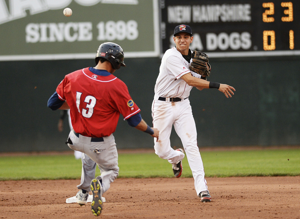 Shawn Patrick Ouellette/Staff Photographer Mauricio Dubon of the Sea Dogs turns a double play as New Hampshire's Emilio Guerrero tries to break up the play at second in Wednesday night's game at Hadlock Field.