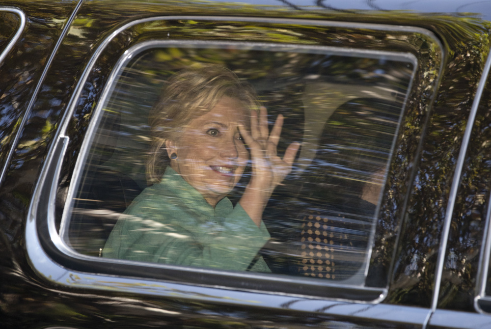 Hillary Clinton waves from her vehicle as she arrives for a fundraiser at the home of Justin Timberlake and Jessica Biel in Los Angeles on Tuesday.