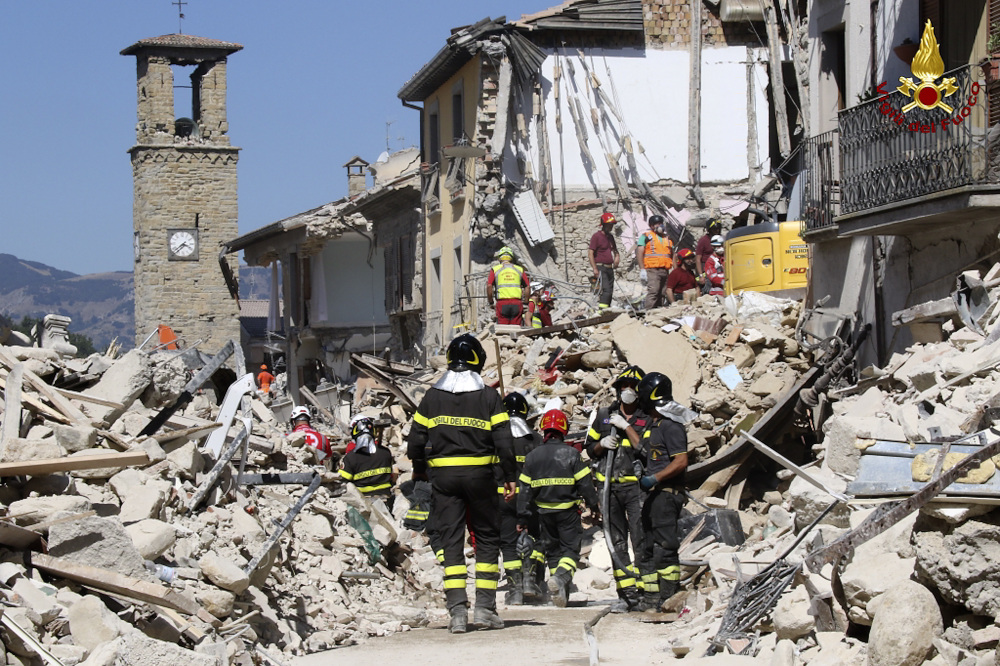 Rescuers work amid collapsed buildings in Amatrice, Italy, on Thursday. Rescue crews raced against time looking for survivors of the earthquake that leveled three towns in central Italy.