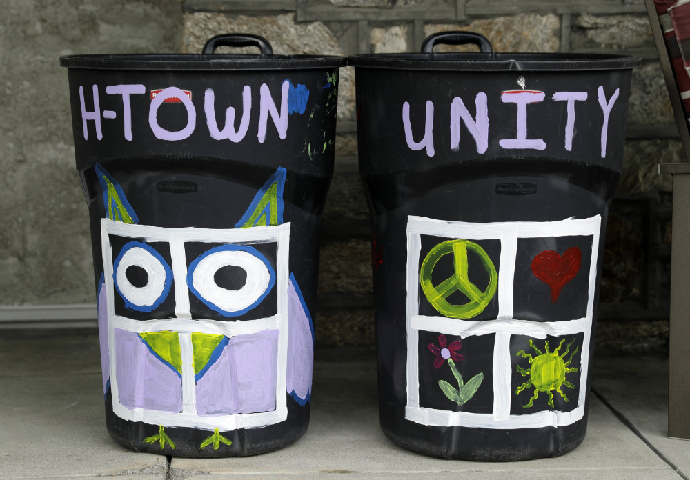 Megan Connell painted her trash cans, left, to show support for her neighbor whose trash bin was defaced with a swastika in Havertown, Pa. Esther Cohen-Eskin painted a flower over the swastika on her garbage can, above, and her neighborhood has rallied around the Jewish family.