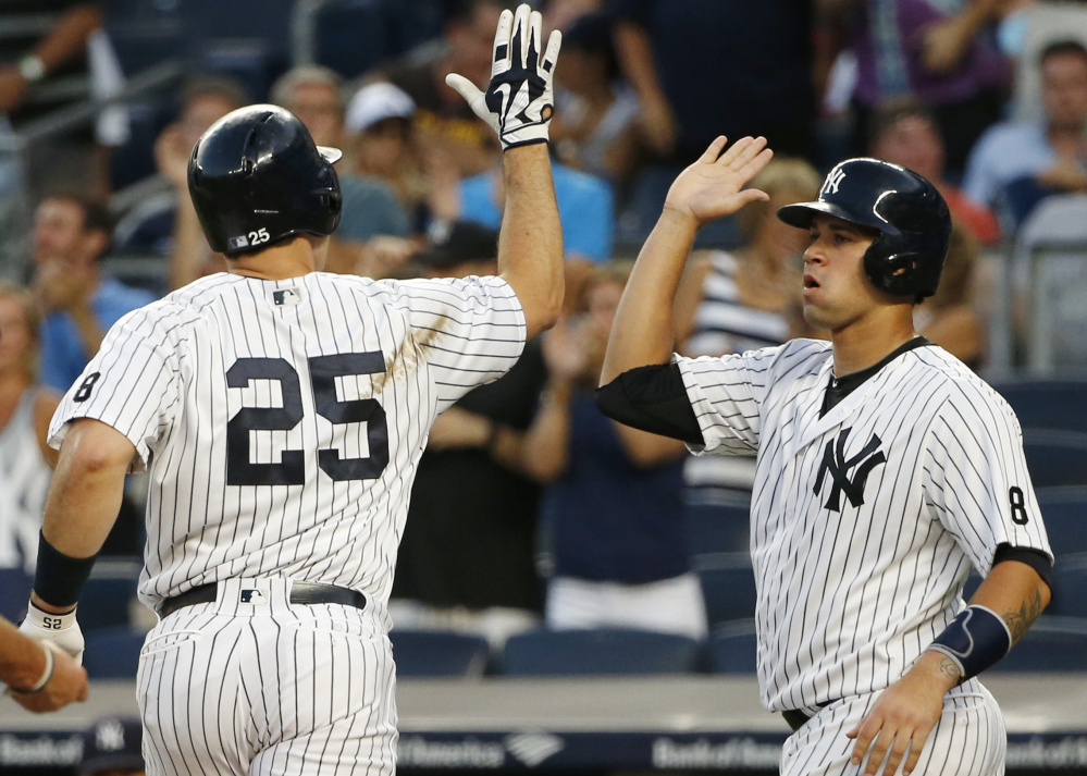 Gary Sanchez, right, greets Yankees teammate Mark Teixeira after scoring on Teixeira's first-inning, two-run homer against Baltimore on Friday. Sanchez also went deep for host New York.