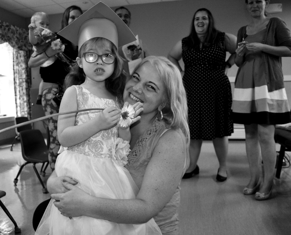 Fraser-Ford Child Development Center ed tech Melissa Chrusicel hugs her student Natalie moments after the conclusion of graduation ceremonies, surrounded by parents and staff at Waban's Wormwood Center.