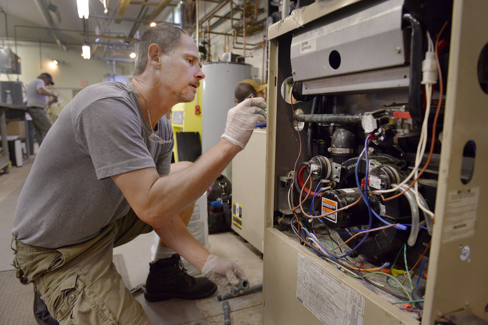 Steven Sweet works on a gas furnace. Strong job growth is forecast for the HVAC industry.