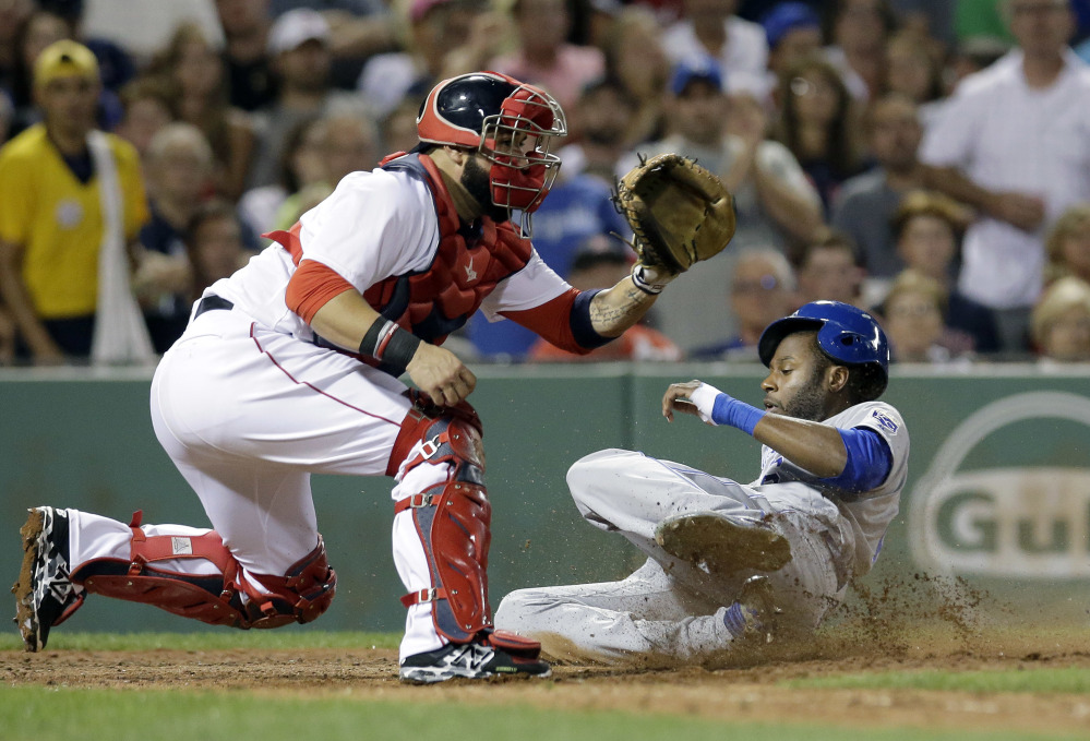 Kansas City's Lorenzo Cain slides safely at home as Red Sox's Sandy Leon waits for the ball in the sixth inning Sunday in Boston.