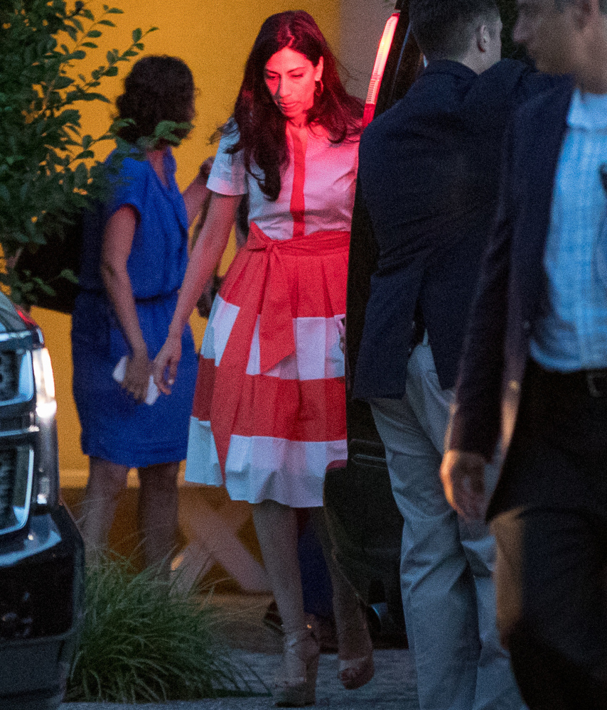 Democratic presidential candidate Hillary Clinton's senior aide Huma Abedin, center, leaves a fundraiser at a private home in Southampton, N.Y., on Sunday.