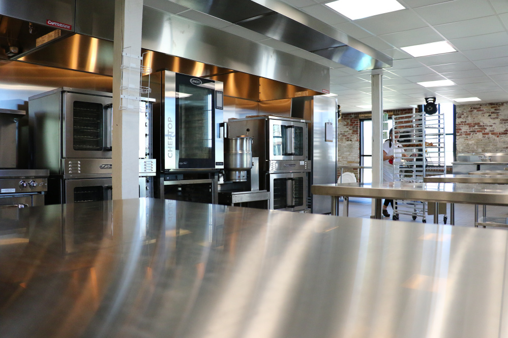 Christina Morrison of Have Chef Will Travel catering company works in the shiny new kitchen.