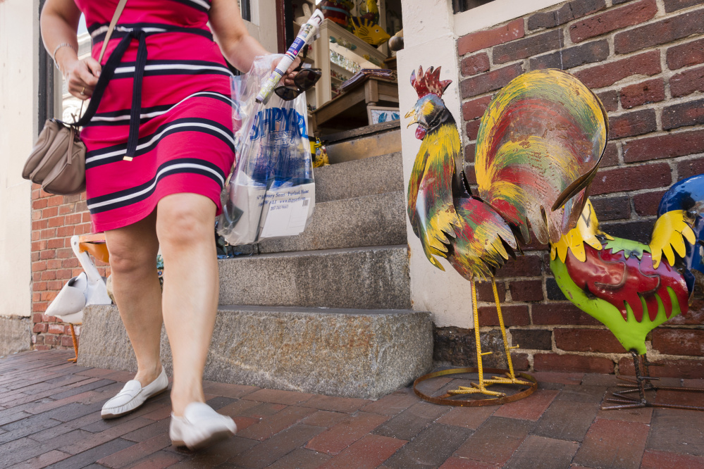 A shopper leaves the Maxwell Pottery Outlet in Portland's Old Port, a popular destination for visitors. Some tourism officials received emails over the weekend from travelers who were canceling trips or saying they won't return.