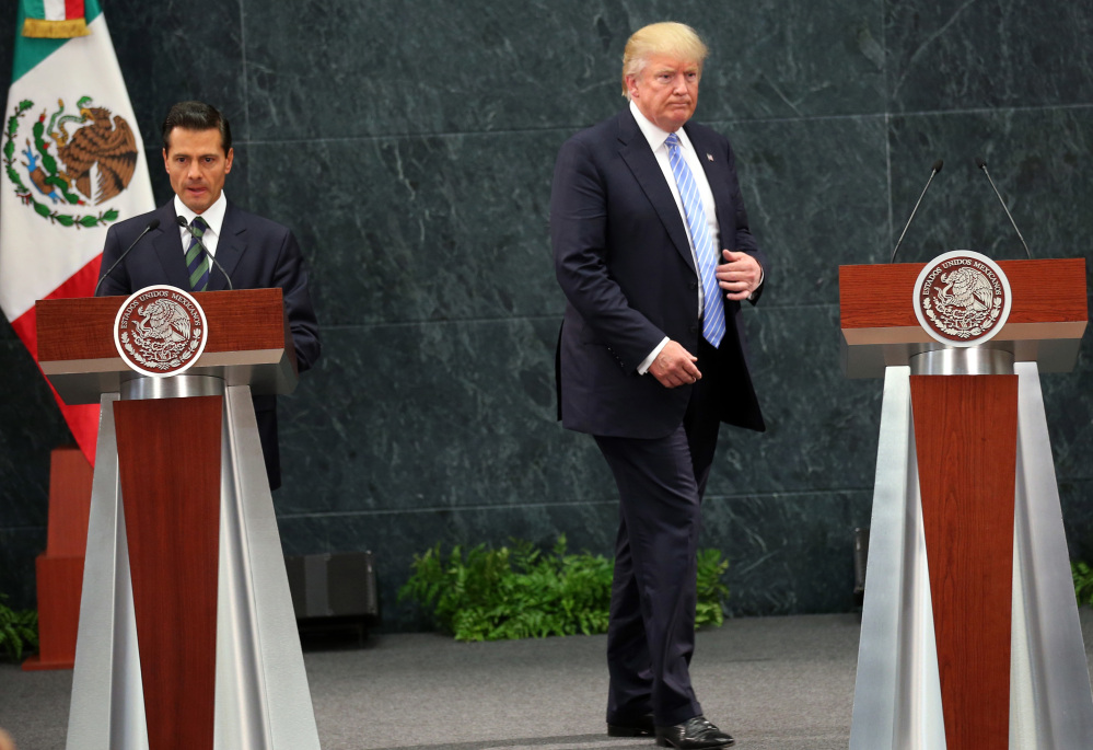 Donald Trump walks to take his place as Mexico's President Enrique Pena Nieto prepares to speak Wednesday during a joint statement at Los Pinos, the presidential official residence in Mexico City.