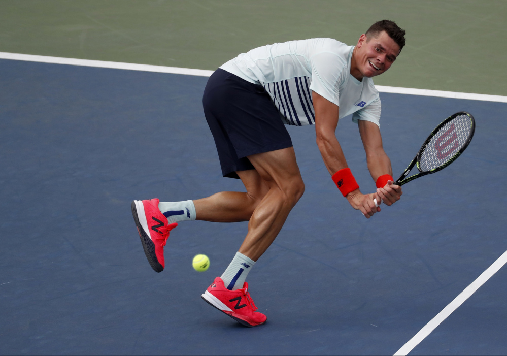 Milos Raonic returns a shot to Ryan Harrison in their second-round match Wednesday at the U.S. Open.