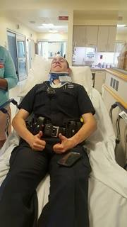Officer Lucas Shirland wears a neck brace in a hospital bed after his cruiser was hit by a drunk driver. Topsham Police Facebook photo