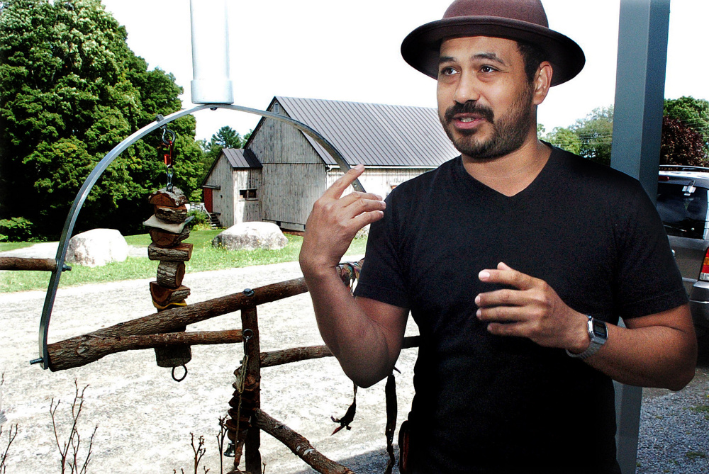 Standing beside a homemade bird perch at the Skowhegan School of Painting and Sculpture in East Madison on Monday, Oscar Cornejo speaks about his escaped parrot Paco that he has been searching for since the bird flew away Thursday.