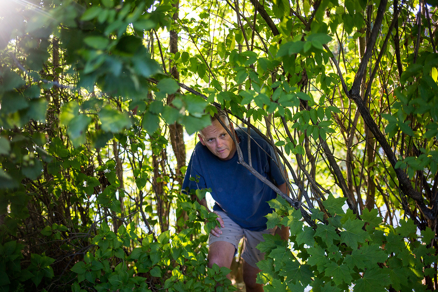 "David Corker emerges from the spot near the Presumpscot River where he found a 12-foot snakeskin Saturday. ""I thought, this is definitely not a garter snake,"" Corker said."