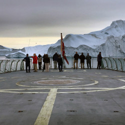 U.S. and Danish defense and meteorological delegations survey an iceberg array off the western coast of Greenland in the summer of 2016.