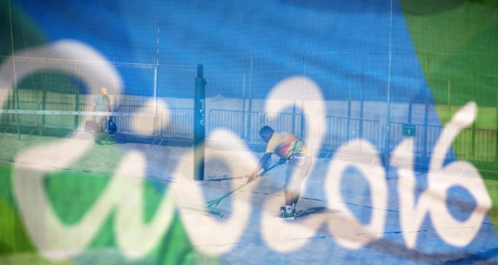 A workers rakes a court after a practice session at the beach volleyball venue on Copacabana Beach on Tuesday in Rio de Janeiro, Brazil.
