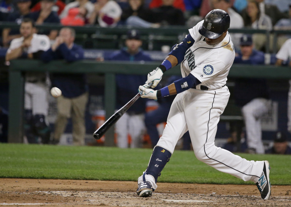 The Mariners' Robinson Cano hits the game-winning three-run homer against Red Sox reliever Fernando Abad in the eighth inning.