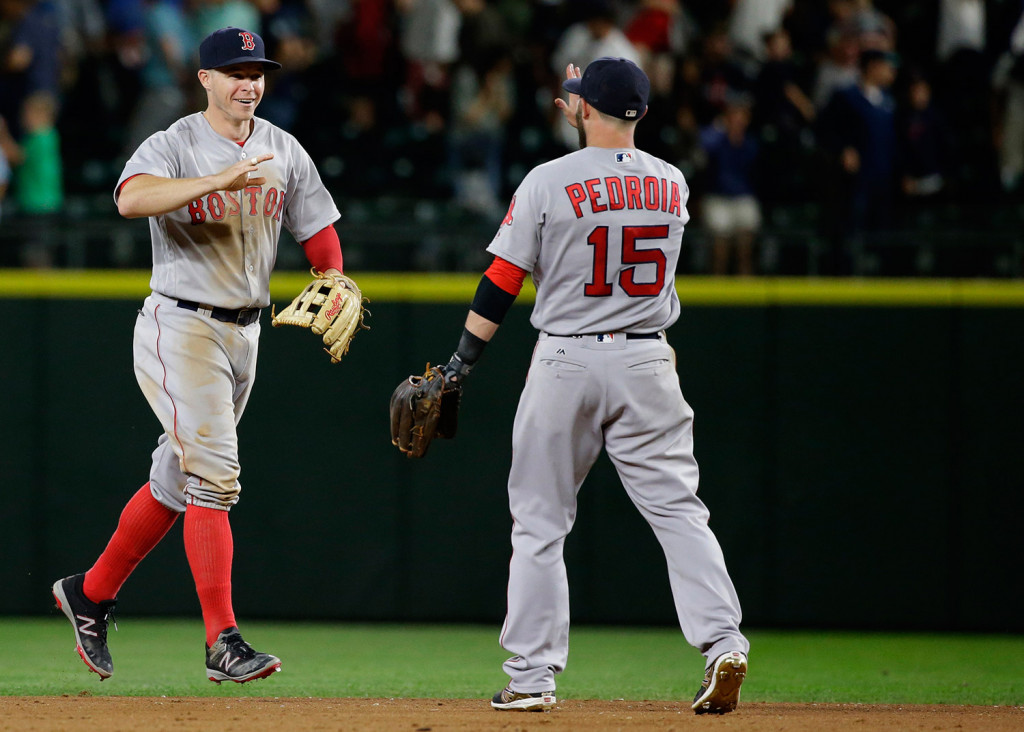 Boston Red Sox outfielder Brock Holt, left, greets second baseman Dustin Pedroia (15) at the end of Thursday's game against the Seattle Mariners in Seattle. The Red Sox beat the Mariners 3-2 in 11 innings.