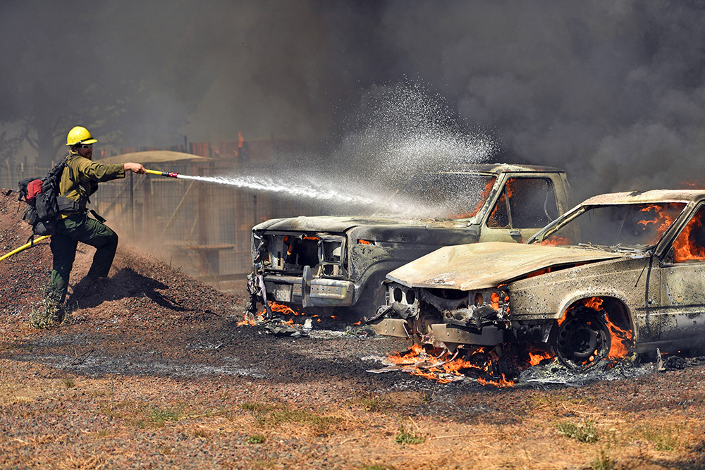 A Cal Fire crewman douses burning cars in the town of Lower Lake, Calif., on Sunday, Flames continued to burn out of control in the area. The fire was creating its own weather pattern and shifted northward into Lower Lake in the afternoon, said Suzie Blankenship, a spokeswoman for the California Department of Forestry and Fire Protection. Josh Edelson/Associated Press
