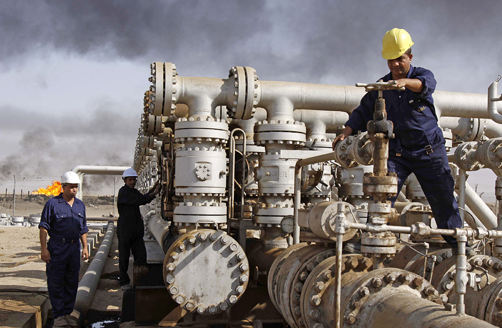 Iraqi workers maintain valves at the Rumaila oil refinery, near Basra, about 340 miles southeast of Baghdad. Donald Trump has said he would have used money from the sale of Iraqi oil to pay for the care of wounded soldiers and the families of those Americans killed in the war. 2009 photo by Nabil al-Jurani/Associated Press