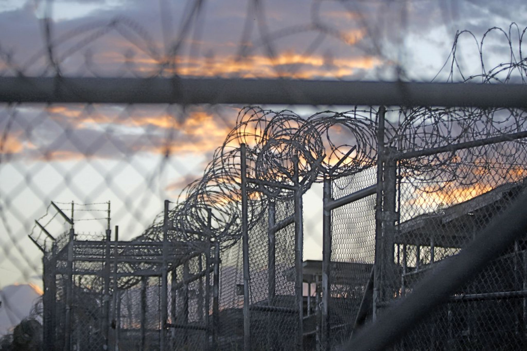 Dawn arrives at the now closed Camp X-Ray, which was used as the first detention facility for al-Qaida and Taliban militants who were captured after the Sept. 11 attacks at Guantanamo Bay Naval Base. An Amnesty International USA official says the prisoner transfers announced Monday are a