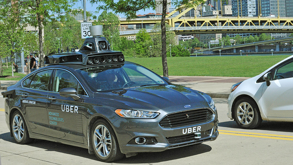 A Ford Fusion hybrid outfitted with radar, laser scanners and high-resolution cameras drives along the streets of Pittsburgh. Uber says customers in the city will be able to summon rides in self-driving cars with the touch of a smartphone button in the next several weeks. Uber photo via AP