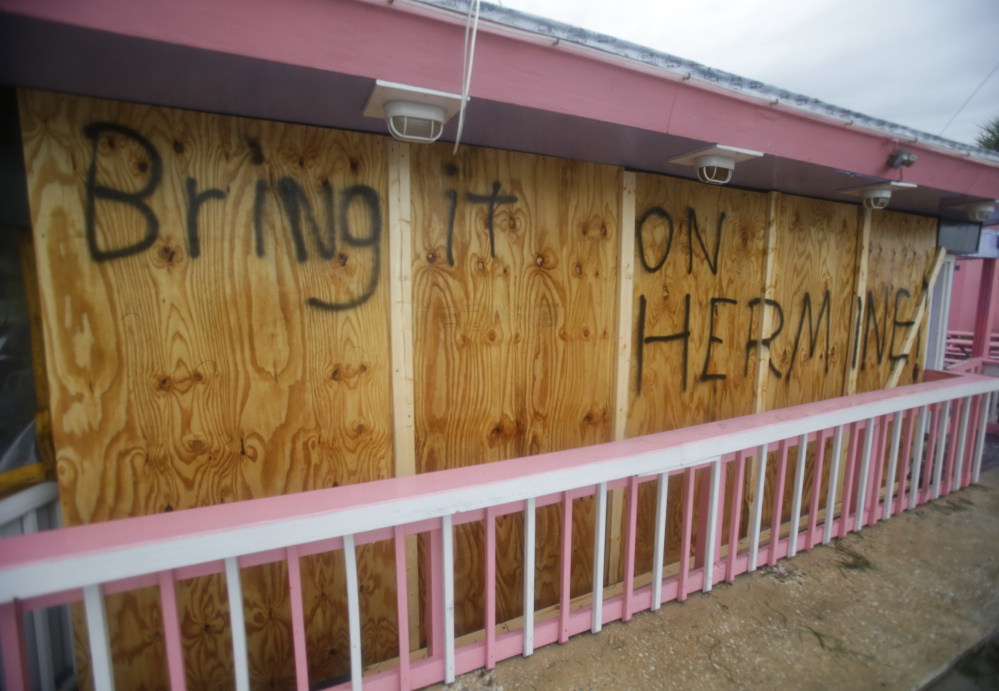 A hand-painted sign on a boarded up bar in Cedar Key, Fla., shows residents' defiance as Hurricane Hermine nears the Florida coast Thursday.