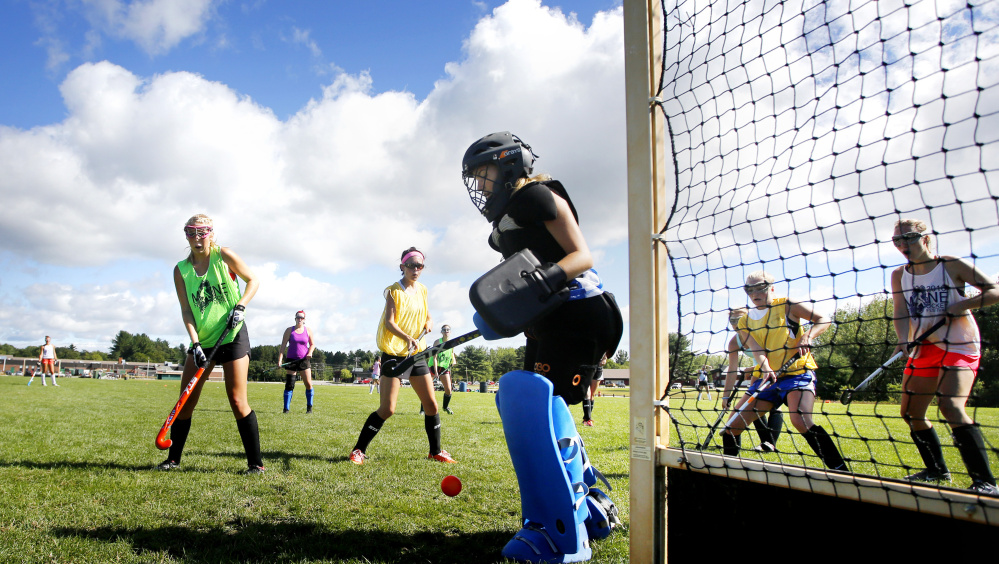 Right now Massabesic is practicing on its old grass field hockey field – Emma Rutledge, left, and Libby Beals look on as Maddy Pomerleau makes a save – but the Mustangs are looking forward to completion of the school's new athletic complex.