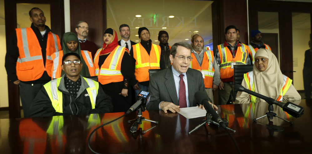 In a photo from earlier this year, attorney Duncan Turner, middle, is backed by workers at Seattle-Tacoma International Airport who sued their employers over the nation's first $15 minimum wage, which they said they did not receive.