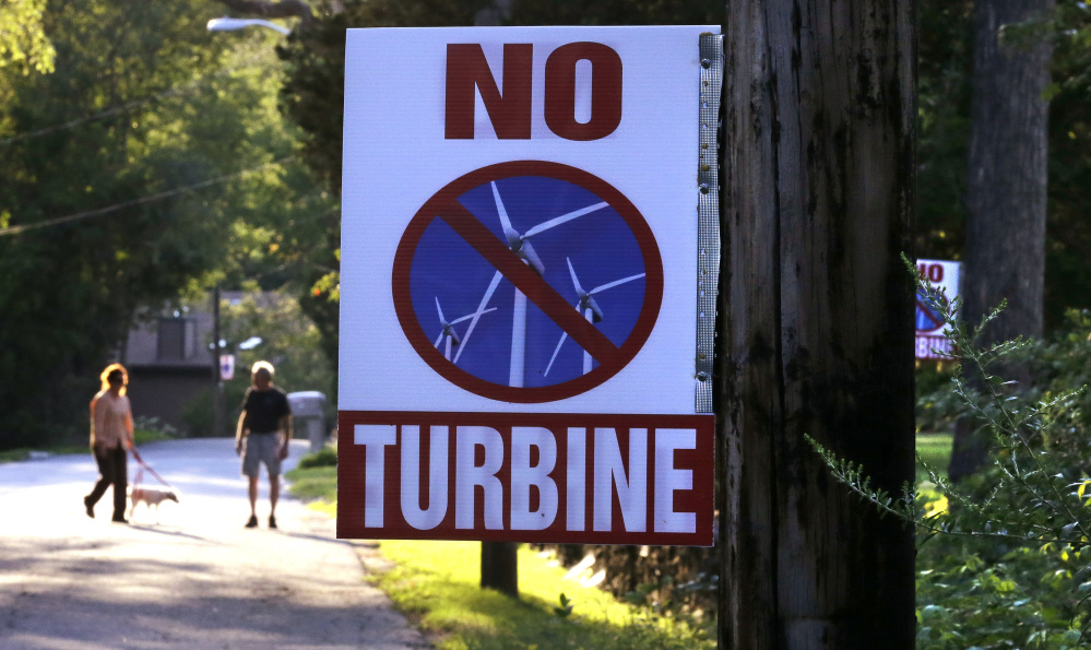 A sign against a proposed wind turbine hangs from a neighborhood telephone pole in North Smithfield, R.I. Even as Rhode Island makes history as the first state with an offshore wind farm, its people are not excited about wind turbines sprouting up on land near where they live.