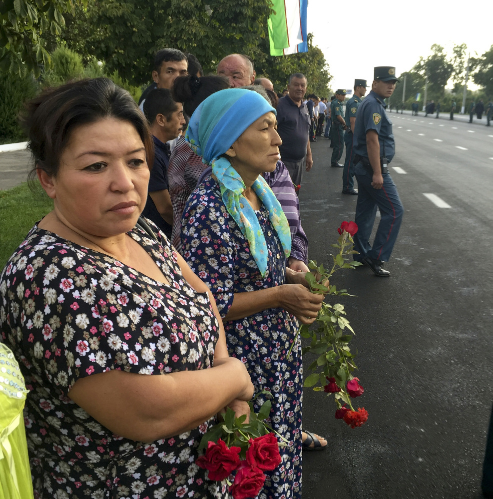 People hold flowers as they gather along the road under the Uzbekistan national flag to watch the funeral procession of President Islam Karimov in Tashkent, Uzbekistan, early Saturday. Karimov died of a stroke at age 78, the Uzbek government announced Friday. Associated Press/ Umida Akhmedova