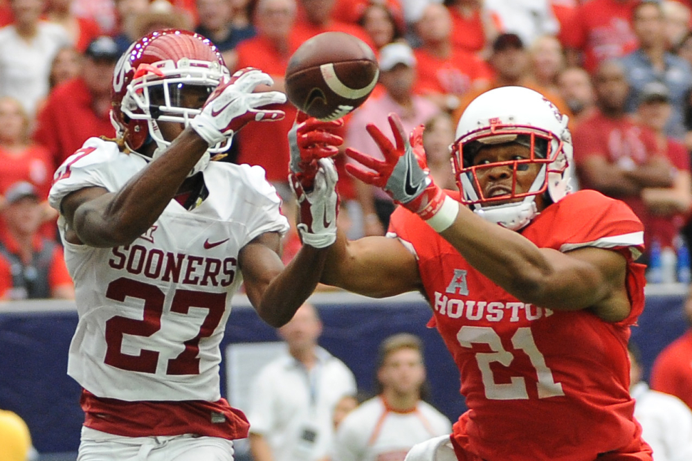 Oklahoma cornerback Dakota Austin, left, and Houston wide receiver Chance Allen reach for a pass that fell incomplete in the second half of Houston's 33-23 victory at home Saturday.