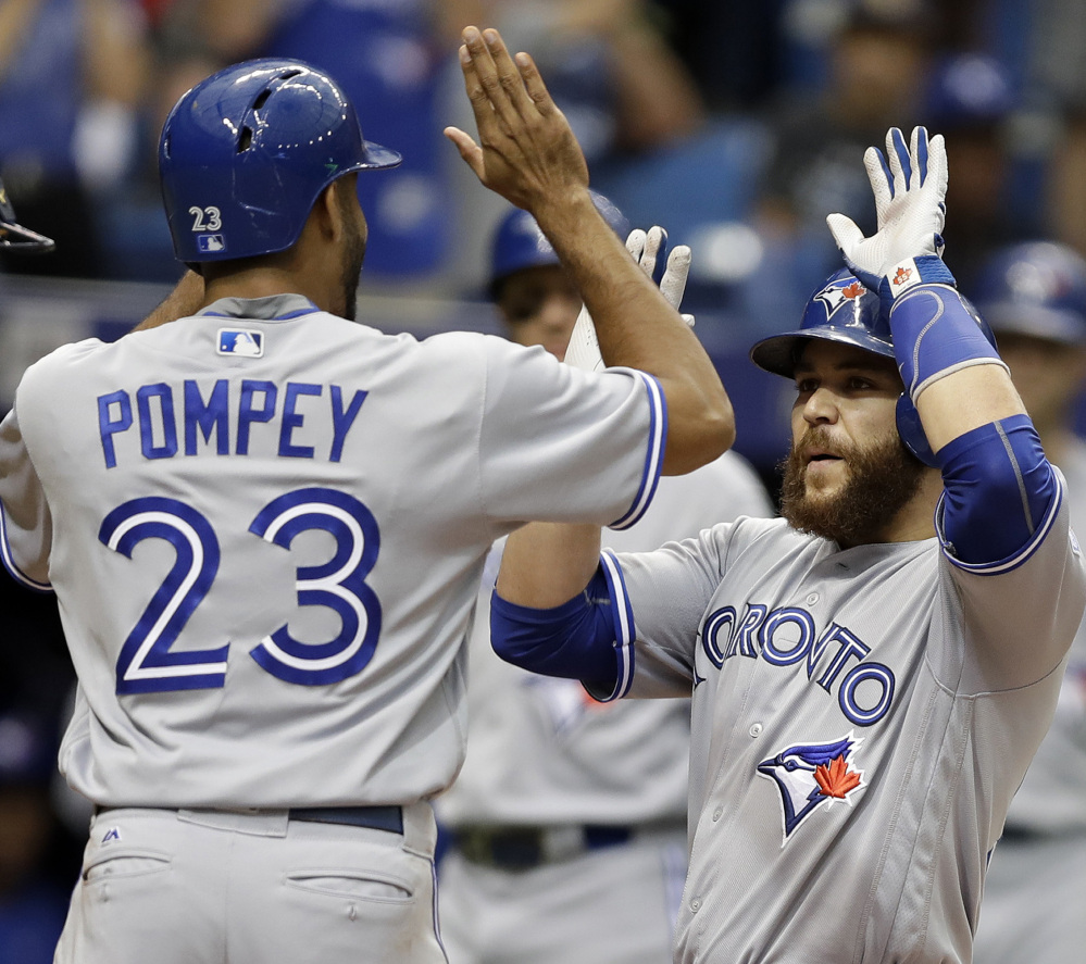 Toronto's Russell Martin celebrates with Dalton Pompey after hitting a two-run homer during a 5-3 win over the Rays at St. Petersburg on Sunday.