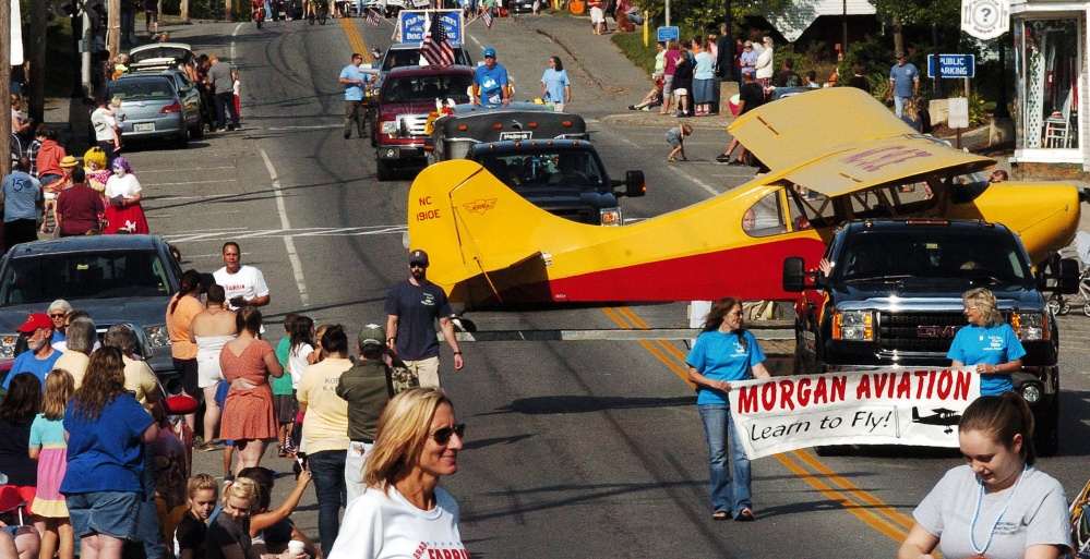A head-turning airplane on a float from Morgan Aviation makes its way down Main Street .