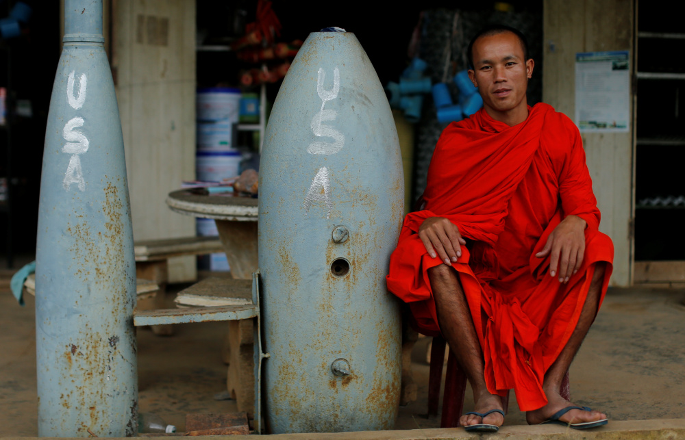 A Buddhist monk sits beside two of the 80,000 unexploded bombs that the U.S. dropped on Laos during the Vietnam War.