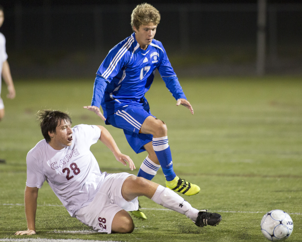 Cape Elizabeth senior Elliot McGinn, left, slides to kick the ball away from Falmouth's Schuyler Parkinson on Tuesday night in Cape Elizabeth. The teams played to a 0-0 tie.