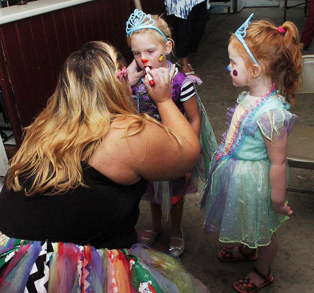 Makayla Bernardini, known as clown character Lovebug, paints the faces of princess clowns Coralie Spencer, left, and Ava Ladd in Clinton on Tuesday.