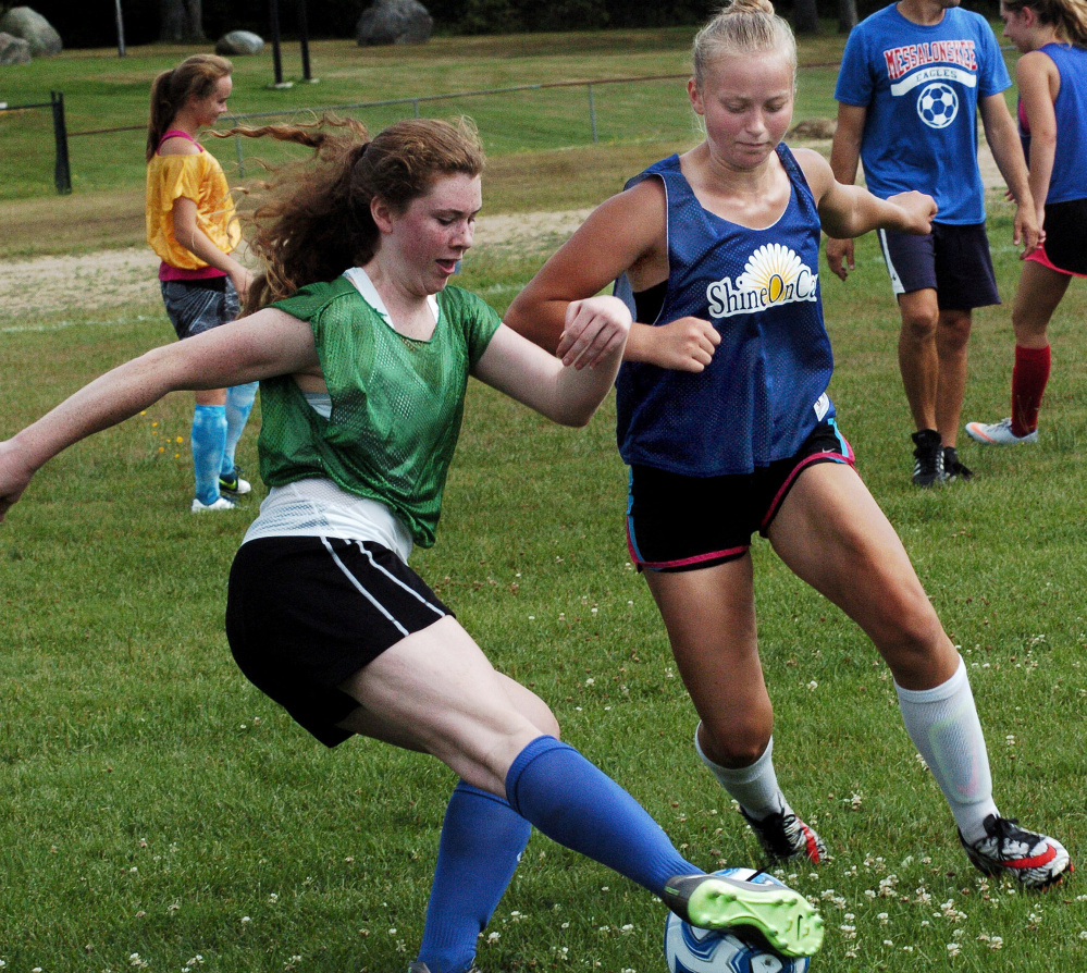 Messalonskee soccer players Ella Moore, left, and Fern Calkins compete during practice on Aug. 15 in Oakland.