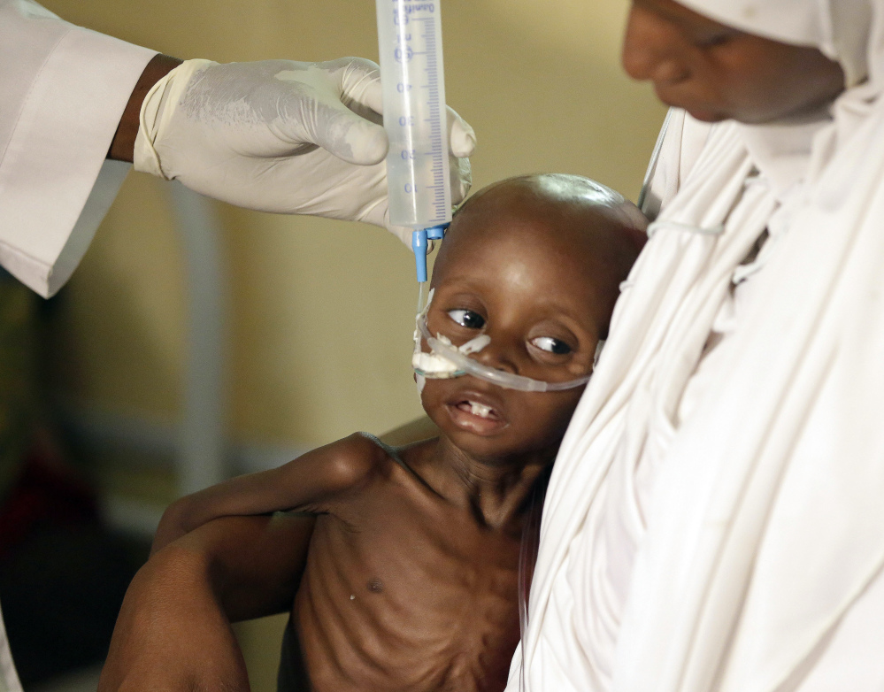 A doctor feeds a malnourished child at a feeding center run by Doctors Without Borders in Maiduguri, Nigeria. A quarter of the children lucky enough to make it to the emergency feeding center are dying.