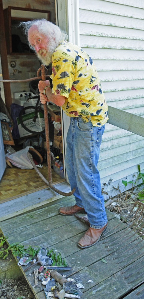 Gary Elwell talks about two items he was able to keep, an antique anchor and pitchfork, a day after the city of Augusta hauled away several dumpsters loaded with debris.