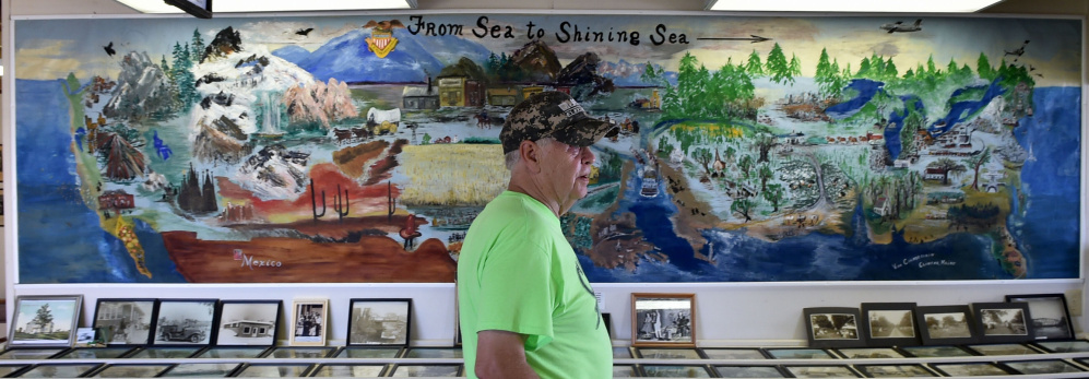 Buddy Frost, president of the Clinton Historical Society, stands in front of a mural painted by Viva Chamberlain in 1976 that's on display at the Clinton Lions Agricultural Fair in Clinton.