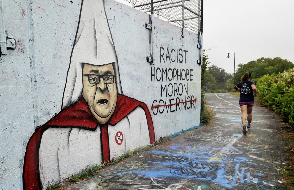 A jogger passes a wall with graffiti depicting Gov. LePage in Ku Klux Klan regalia along the Eastern Promenade Trail in Portland last Tuesday. The mural galvanized debate in many forms – including online comments, handwringing by public officials and the alteration of the image by other graffiti artists.