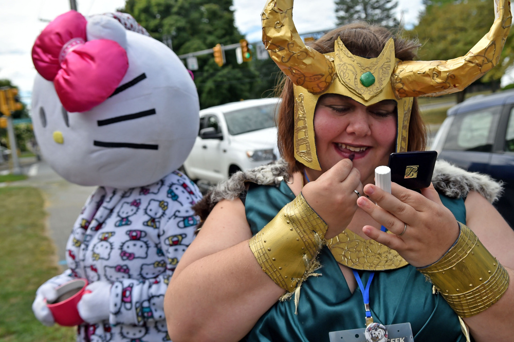 Emily Fournier, right, applies makeup to her fictional sci-fi character Loki Lady costume Saturday at the Waterville Public Library for the Cirque du Geek convention's parade.
