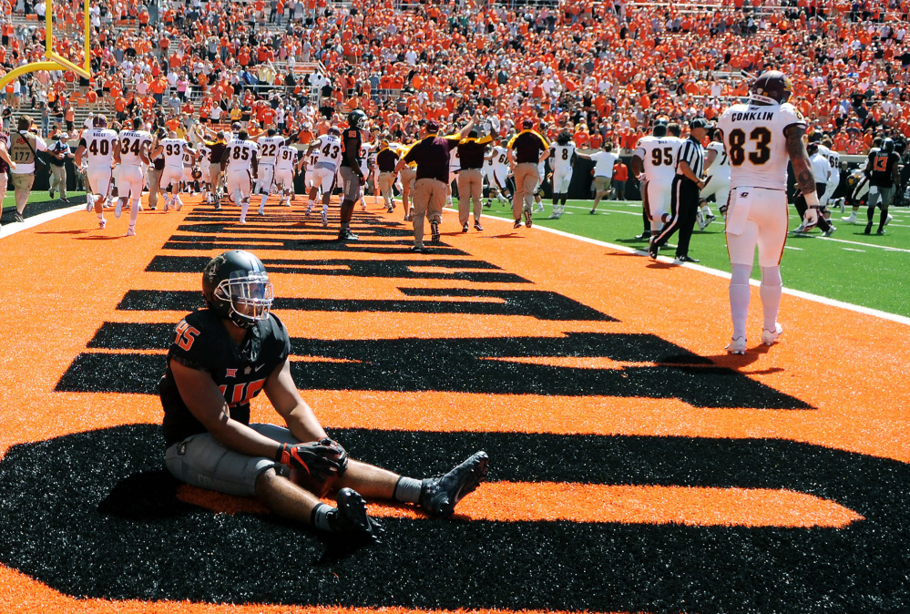 Oklahoma State linebacker Chad Whitener sits alone in the end zone while Central Michigan celebrates a last-second touchdown by receiver Corey Willis that gave the Chippewas a 30-27 win Saturday in Stillwater, Okla.